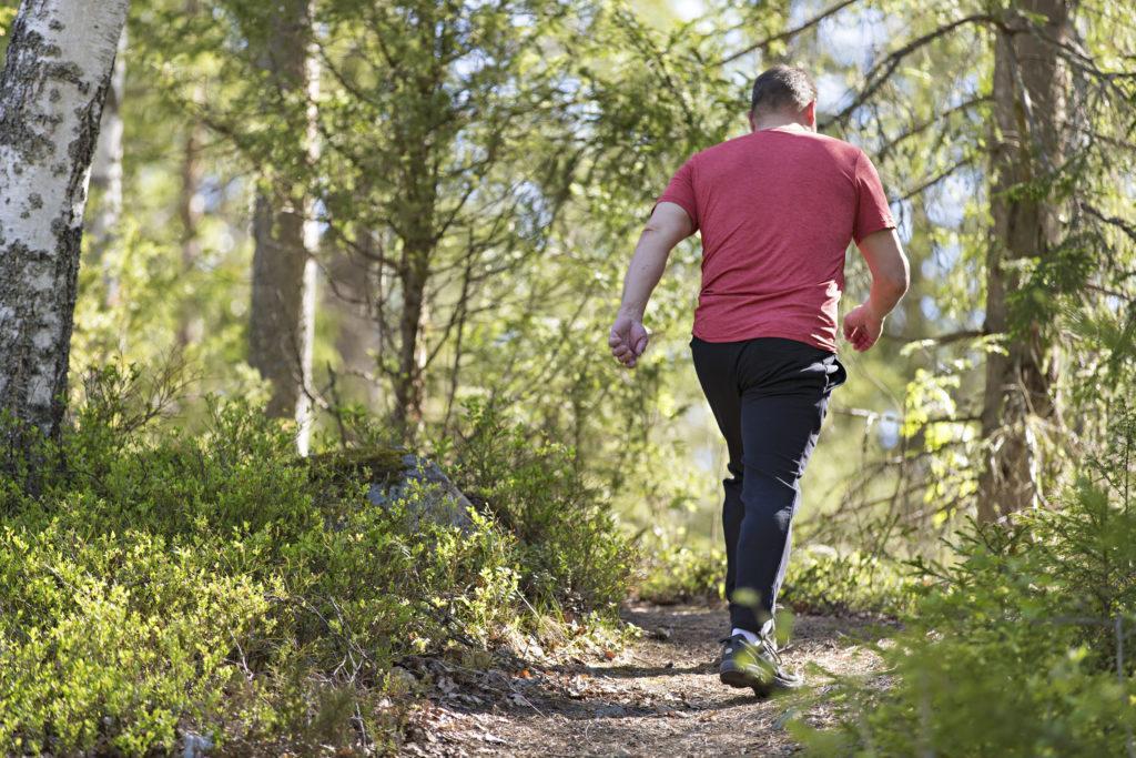 Mies kävelee metsäpolulla