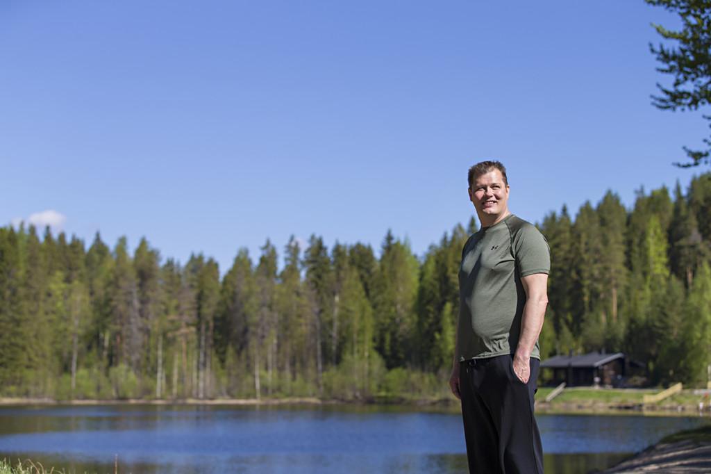 Mies seisoo järven rannalla