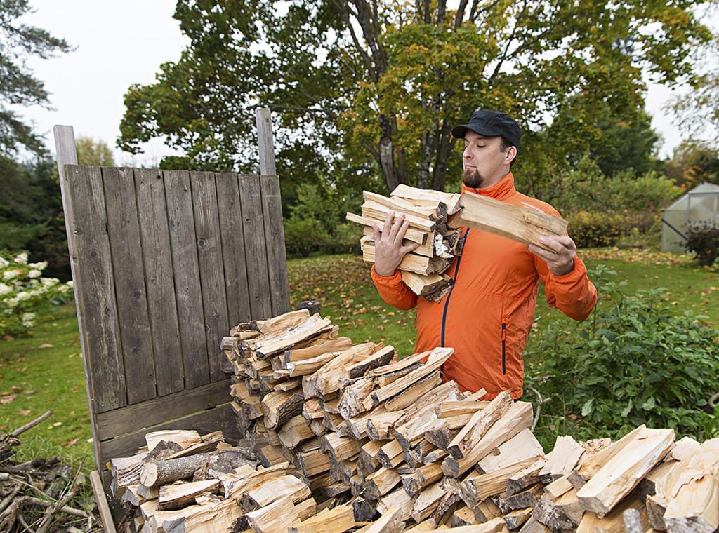 Mies latoo puita syliin halkopinolla