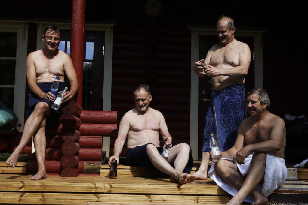 Miehet istuvat portailla rantasaunan edustalla