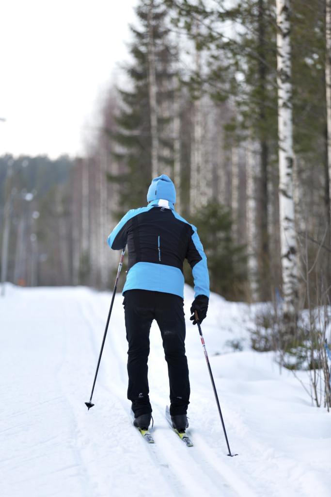 Mies hiihtää ladulla