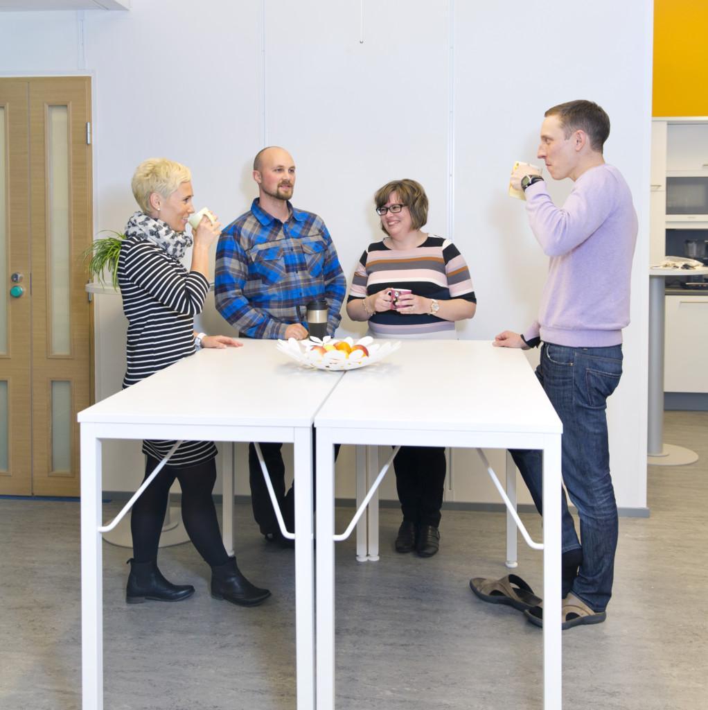 Neljä henkilöä seisoo kahvitauolla pöydän ympärillä.