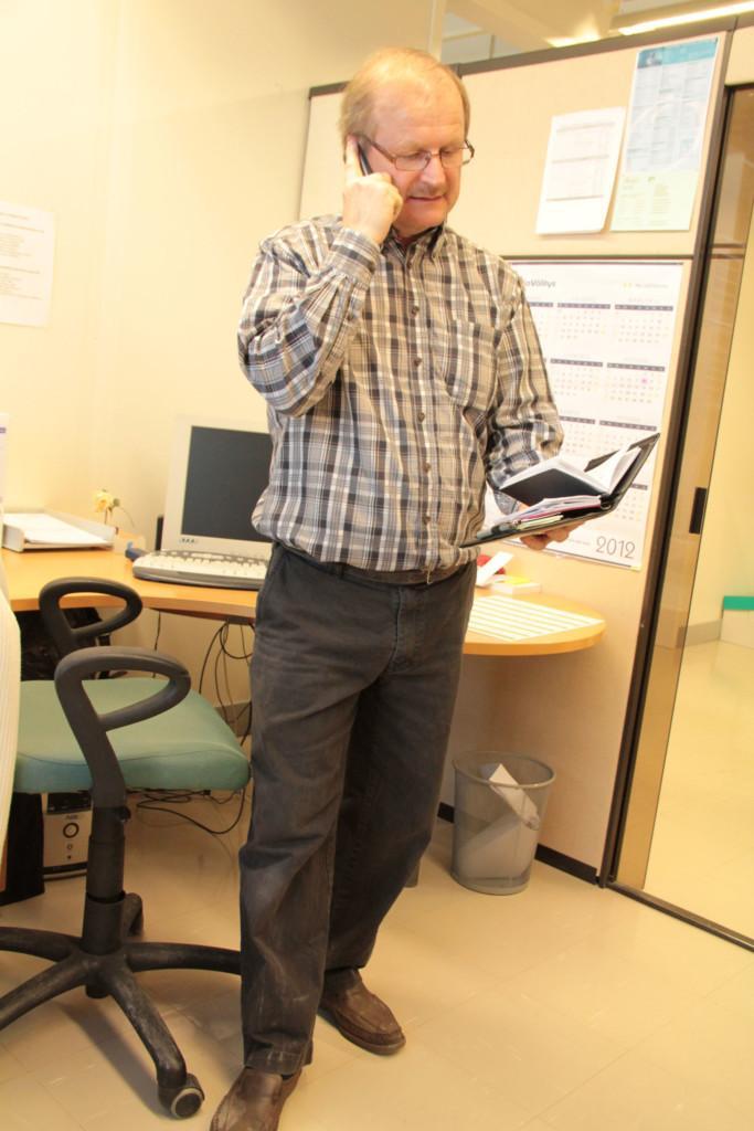Mies seisoo ja puhuu puhelimeen kalenteriaan katsellen.