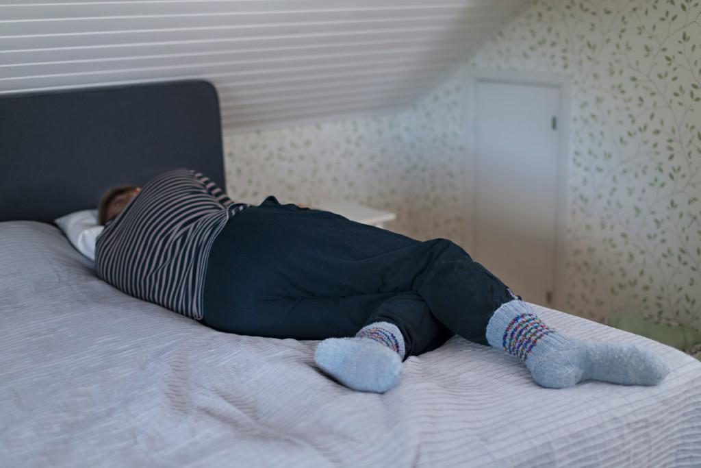 Mies nukkuu päiväunia sängyllä.