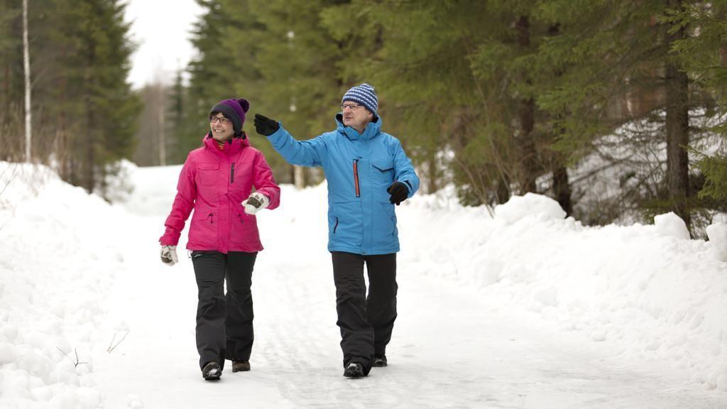 Mies ja nainen kävelevät lumisella tiellä.