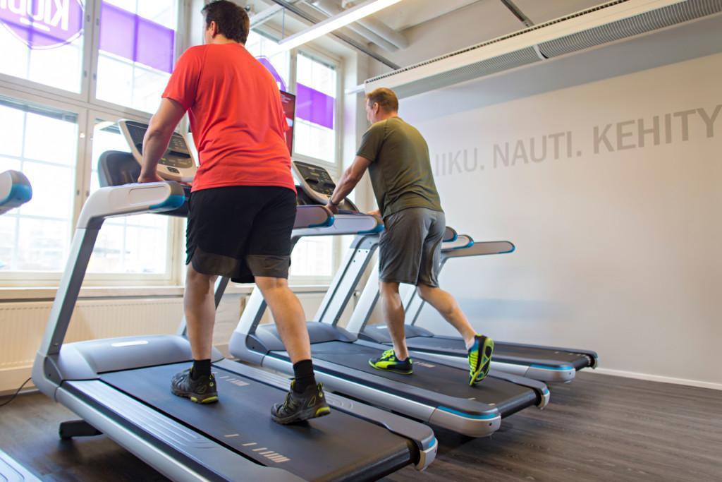 Kaksi miestä juoksee tai kävelee juoksumatolla kuntosalilla.