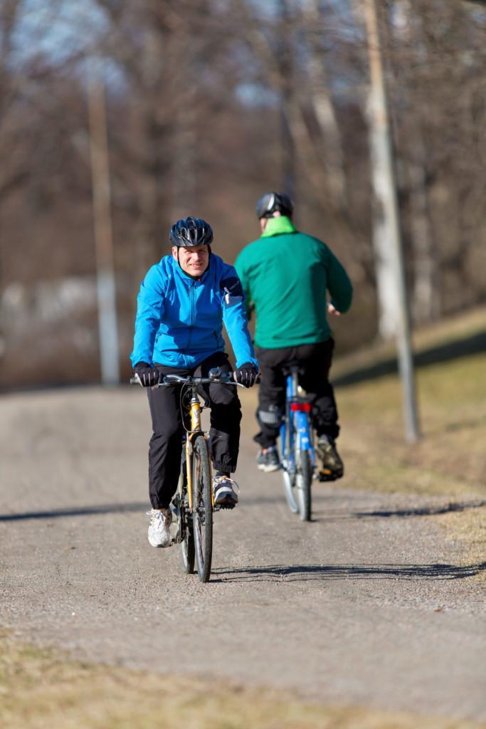 Kaksi miestä pyöräilee hiekkatiellä.