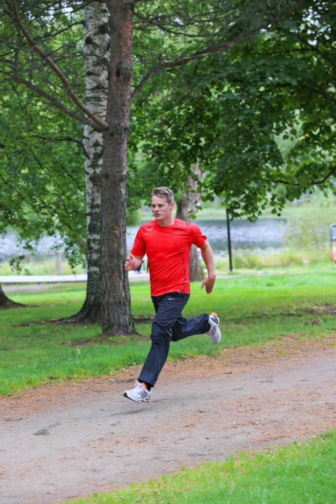Punapaitainen ja mustahousuinen mies juoksee pitkillä askeleilla pitkin hiekkakäytävää. Taustalla on nurmikkoa ja lehtipuita.
