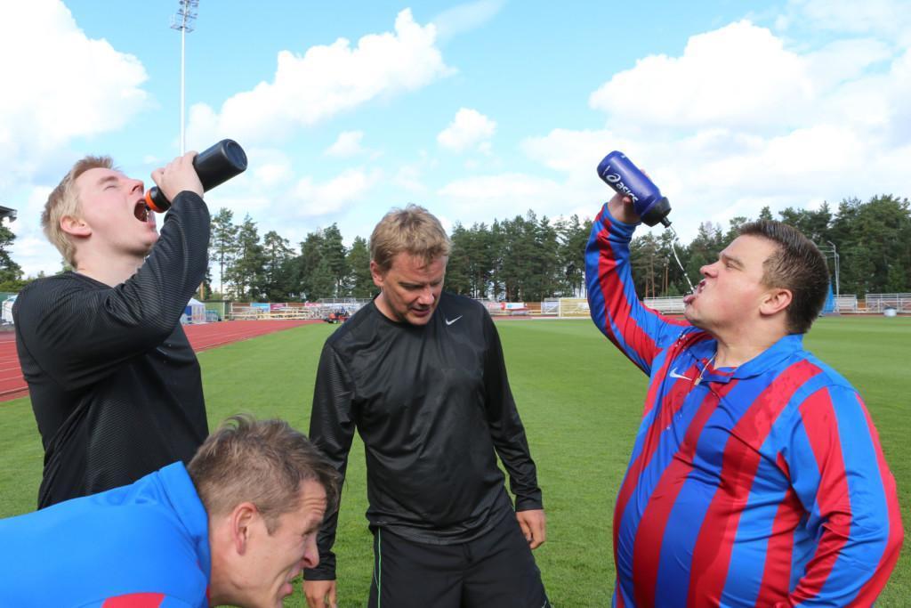 Neljä miestä seisoo jalkapallokentällä. Kaksi miestä juo juomapulloista vettä ja kaksi muuta miestä huilaa.